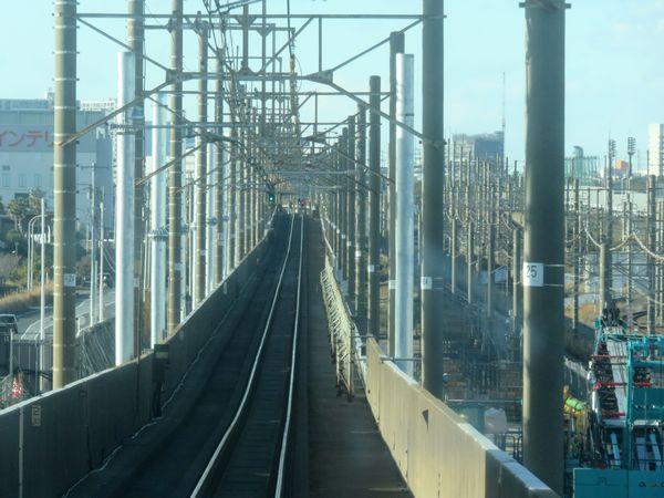 上り列車の前面展望。左側から片持ちの電化柱を新設中。