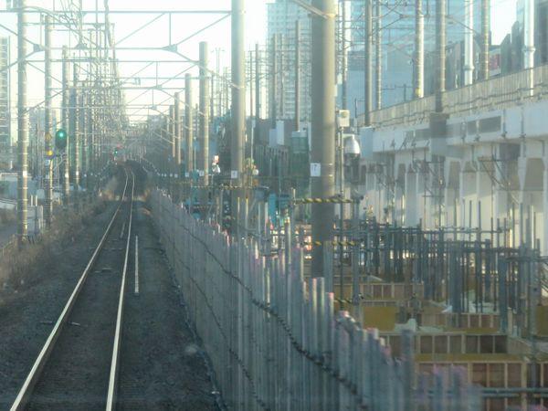 下り列車の前面展望。右側で型枠が組まれ、下りホーム用の土台コンクリートを構築中。