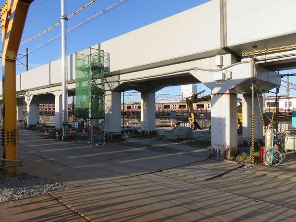 バスターミナルのフェンス越しに見た新駅予定地。奥では地上から高架橋の基礎となる鉄筋が飛び出しているのが見える。