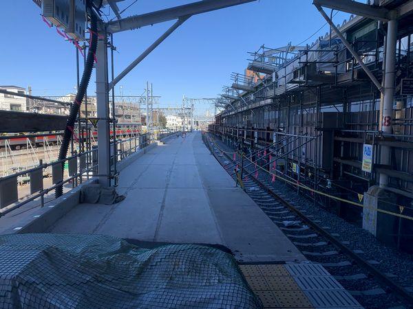改札口から上りホームへ向かう通路から見た建設中の新上りホーム。現ホームを避けるためカーブしている。