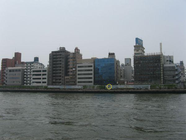 左岸から東京方面を見る。トンネルは正面のガラス張りのビルの下に向かって進んでおり、手前の護岸に埋設物表示がある(黄色で丸く囲んだ部分)。